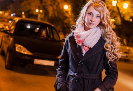 Young blond 20s female walking on the street against car photo