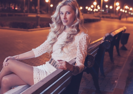 20 to 25 years old: 20s blond women outdoor sitting on the park bench with street lights