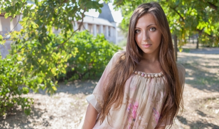 The beautiful young woman with long hair in dress  outdoor photo