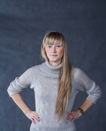 Blonde women looking at camera studio shot. Portrait of elegant young woman in a jumper  on a dark background Stock Photo - 23053404