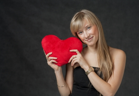 Pretty blond haired women with her heart in hands. Beautiful young woman holding a heart shaped red pillow and smiling Stock Photo - 23053605