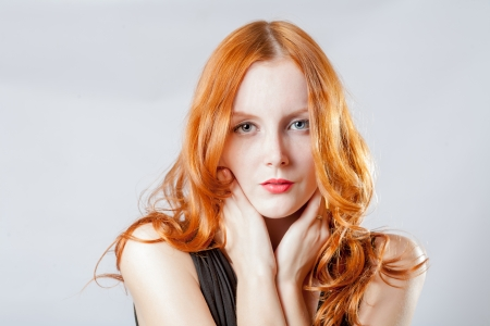 Horizontal beauty shot of a young blue eyed woman with her red hair, touching face by her hands, looks very shy photo