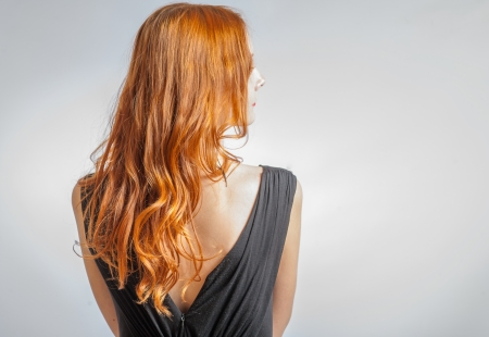 back straight: Back view of Red curly long hair of Beautiful Woman with a lot of copyspace
