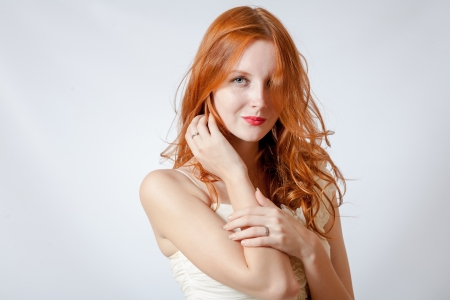 A beauty shot of a young blue eyed woman with her red hair photo