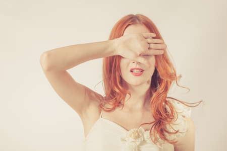 Toned image. Young redhead woman, girl covering her eyes on white background. Covered her eyes with her hands photo