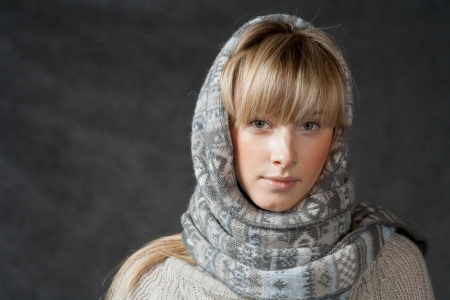 winter fashion shot of a beautiful girl with long curled blonde hair wearing a grey woolen cap and grey sweater photo