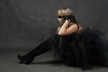 Blindfolded female sitting on the floor and dreaming  She weared black tutu skirt photo