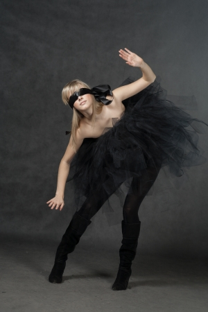 Blindfolded girl full body shot  She weared black tutu skirt  Studio shot on black background photo