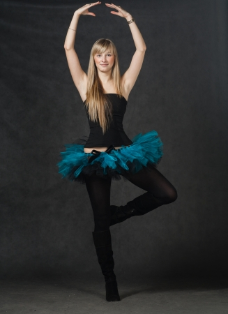 young beautiful dancer with blond hair dancing on a dark studio background Stock Photo - 23216882