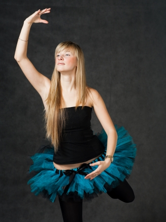 Torso shot of the young beautiful dancer with blond hair dancing on a dark studio background photo