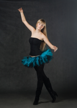 young beautiful dancer with blond hair dancing on a dark studio background photo
