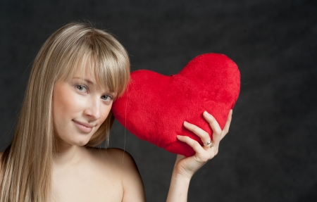 American Blond haired Woman with a Heart-Shaped Cushion on dark background photo