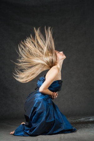 Beautiful 20s female with flying blond hair studio shot on the dark background photo
