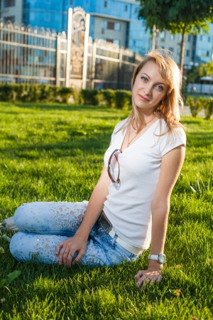 blond sitting on the fresh grass against sun photo