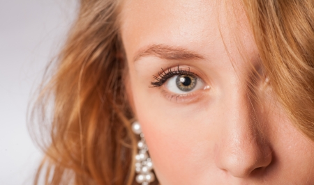 half part of the face of the blond haired female, focus on  eye photo