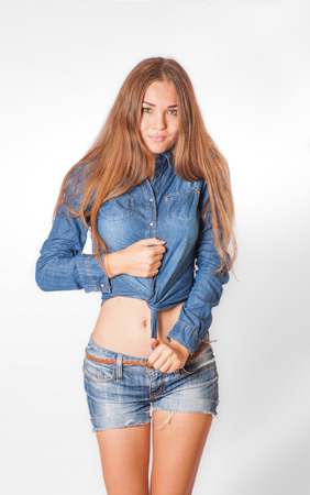 sexy long haired blonde female in jeans, studio torso shot on white photo