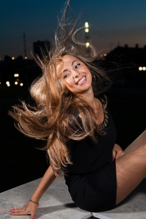 wind in hair  long haired blond women at night in city park photo