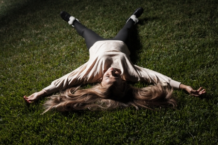 Young attractive blonde woman lay on grass photo