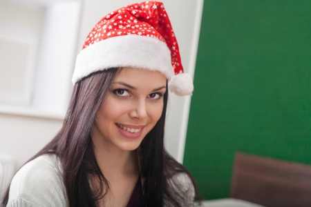 mrs  Santa smiling, 20s brunette women in santa hat,  indoor photo