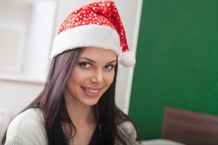 mrs  Santa smiling, 20s brunette women in santa hat,  indoor Stock Photo - 23728854