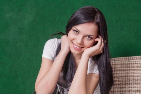 brunette indoors sitting against green wall and smiling photo
