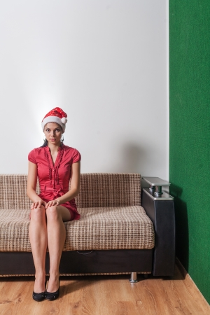 20s female in red Santa Hat full body shot  Cute brunette weared red dress sitting on sofa indoors photo