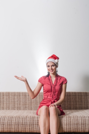 happy mrs  Santa indoors sitting on sofa and pointing Stock Photo - 23728886