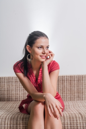 smiling brunette weared red dress sitting on sofa indoors photo