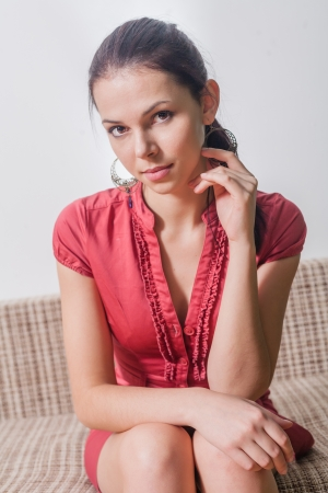 brunette looking at camera  20s female weared red dress sitting on sofa indoors photo