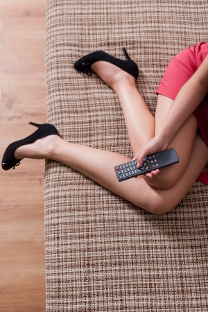 View from above , remote control in hands and young women legs, indoor photo