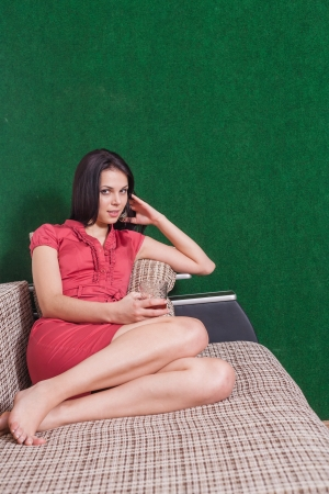brunette weared red dress sitting on sofa indoors photo