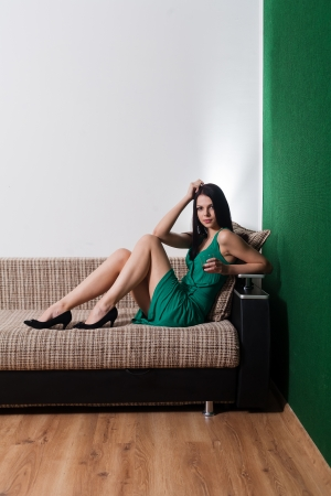 brunette sitting on sofa, vertical shot Stock Photo - 23728893