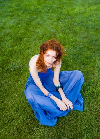 redhead  women meditating on grass Stock Photo