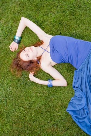 redhead women on grass daydreaming Stock Photo