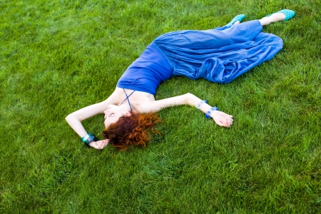 rd haired women laying on grass and watching clouds Stock Photo