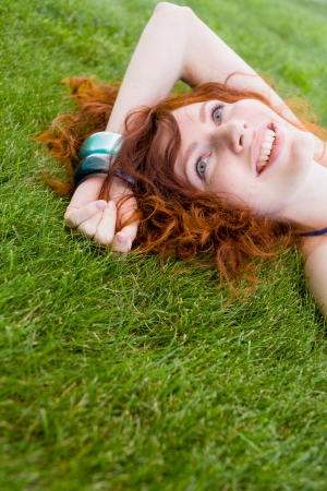 redhead smiling on grass, face closeup