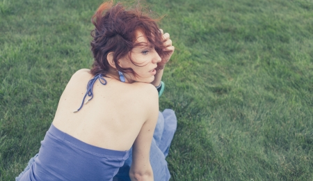 redhead sitting on grass, backview, toned image photo