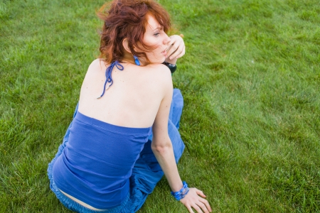 red haired female sitting on fresh grass, back view Stock Photo