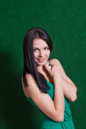 brunette weared green dress smiling against green wall photo