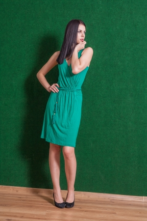 brunette weared green dress standing indoors, against green wall photo