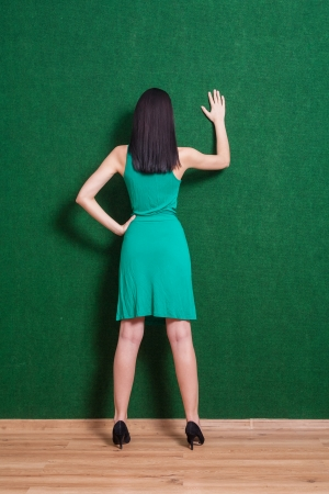 brunette gesturing against green wall  Hand up  photo