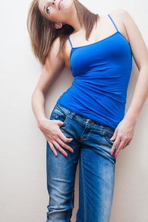 mid-section of the female weared blue tank top and jeans photo