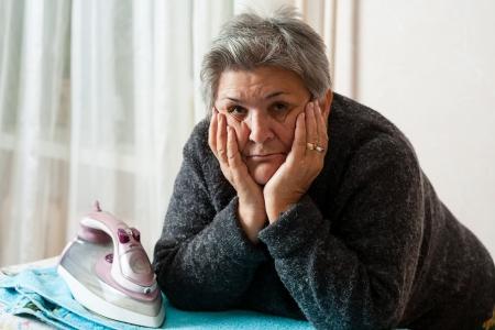 indoor shot: Mujeres mayores plancha de ropa, tiro de interior