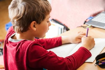 studing: boy writing indoors Stock Photo
