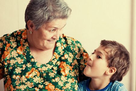 grandma and grandson indoors looking on each other photo