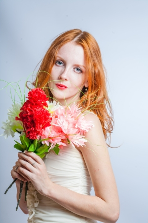 blank expression: Cute 20s female with pretty flowers. Redhead women with bunch of flowers in studio on white. Blank expression.