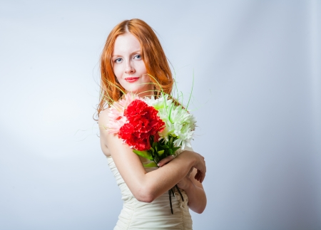 Horizontal image of redhead with bunch of flowers in studio on white. She looking at camera photo