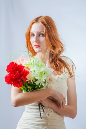 Vertical image of the redhead with bunch of flowers in studio on white photo