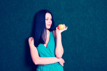 cross processed: Cute girl looking away. Young women with apple in hand