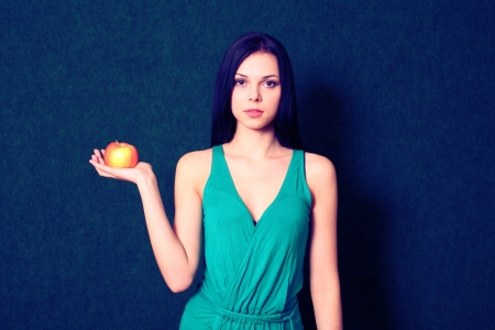 cross processed: Cross processed image of young women with apple in hand Stock Photo